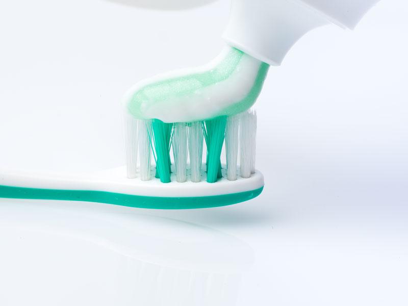 Zahnpasta wird auf einer Zahnbürste verteilt